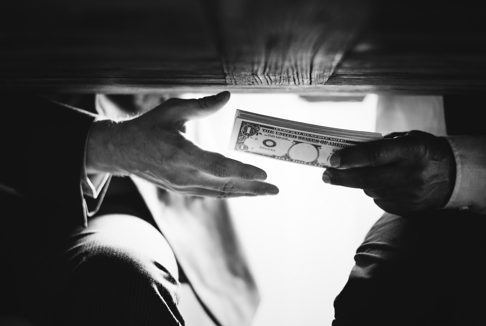 Hands passing money under table corruption bribery